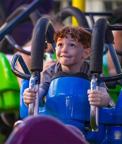 A boy enjoying a Fair ride.