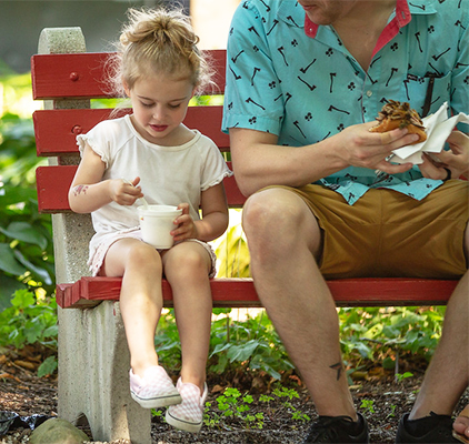 A girl on a bench with her father eating ice cream