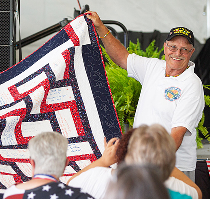 A man displaying a quilt